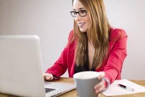 Femme qui travail sur un ordinateur avec une tasse de thé à la main